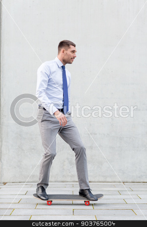 young smiling businessman with skateboard outdoors stock photo, business, hot drinks and people and concept - young smiling businessman riding on skateboard outdoors by Syda Productions