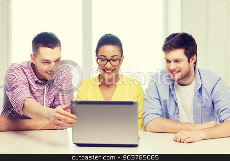 three smiling colleagues with laptop in office stock photo, education, technology, business, startup and office concept - three smiling colleagues with laptop in office by Syda Productions