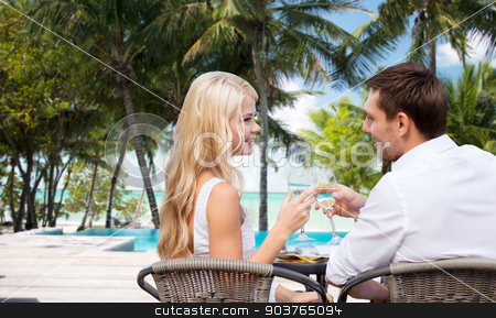 couple drinking wine in cafe on hotel beach stock photo, summer holidays, travel, tourism, celebration and dating concept - happy couple drinking wine in cafe over hotel beach with swimming pool background by Syda Productions