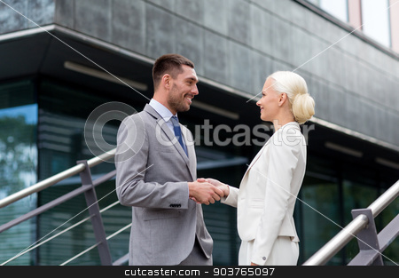 smiling businessmen shaking hands on street stock photo, business, partnership, success, gesture and people concept - smiling businessman and businesswoman shaking hands on city street by Syda Productions