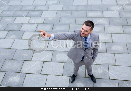 young smiling businessman outdoors from top stock photo, business, development and people and concept - young smiling businessman pointing finger outdoors from top by Syda Productions