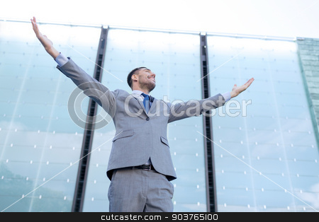 young smiling businessman over office building stock photo, business, people and education concept - young smiling businessman with raised hands over office building by Syda Productions
