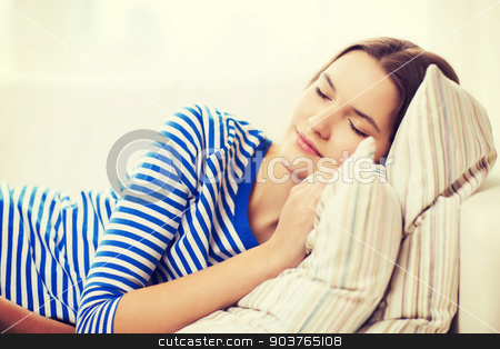 smiling teenage girl sleeping on sofa at home stock photo, home and happiness concept - smiling teenage girl sleeping on sofa at home by Syda Productions