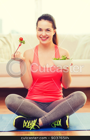 smiling teenage girl with green salad at home stock photo, healt, dieting, home and happiness concept - smiling sporty teenage girl with green salad at home by Syda Productions