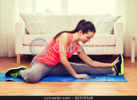 smiling teenage girl streching on floor at home stock photo, fitness, home, technology and diet concept - smiling teenage girl streching on floor with smartphone at home by Syda Productions