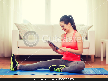 smiling teenage girl streching on floor at home stock photo, fitness, home, technology and diet concept - smiling teenage girl streching on floor with tablet pc computer at home by Syda Productions