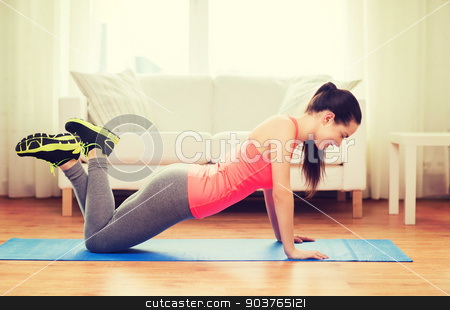 smiling teenage girl doing push-ups at home stock photo, fitness, home and diet concept - smiling teenage girl doing push-ups at home by Syda Productions