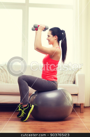 smiling girl exercising with fitness ball stock photo, fitness, home and diet concept - smiling girl exercising with fitness ball and dumbbells at home by Syda Productions