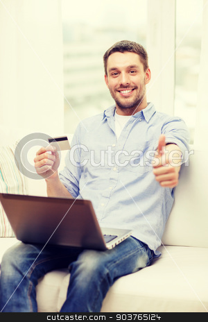 smiling man working with laptop and credit card stock photo, technology, home and lifestyle concept - smiling man working with laptop and credit card at home and showing thumbs up by Syda Productions