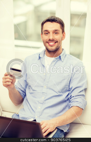 smiling man working with laptop and credit card stock photo, technology, home and lifestyle concept - smiling man working with laptop and credit card at home by Syda Productions