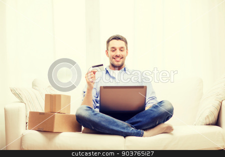 man with laptop, credit card and cardboard boxes stock photo, technology, home and lifestyle concept - smiling man with laptop, credit card and cardboard boxes at home by Syda Productions