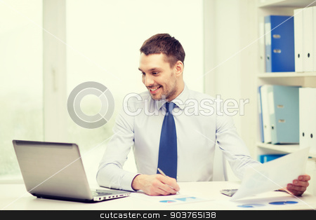smiling businessman with laptop and documents stock photo, office, business, technology, finances and internet concept - smiling businessman with laptop computer and documents at office by Syda Productions