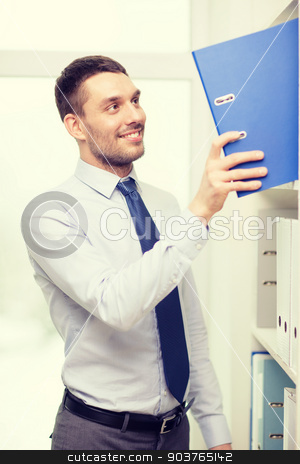 handsome businessman picking folder at office stock photo, business and office concept - handsome businessman picking folder at office by Syda Productions