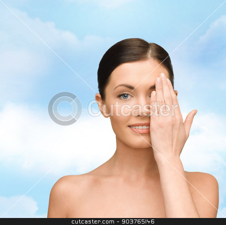 smiling young woman covering face with hand stock photo, beauty, people and health concept - smiling young woman covering half of face with hand over blue sky background by Syda Productions