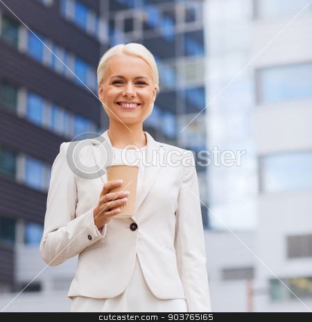 smiling businesswoman with paper cup outdoors stock photo, business, hot drinks and people and concept - young smiling businesswoman with paper coffee cup over office building by Syda Productions