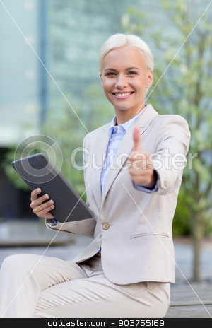smiling businesswoman with tablet pc outdoors stock photo, business, education, technology, gesture and people concept - smiling businesswoman working with tablet pc computer showing thumbs up on city street by Syda Productions