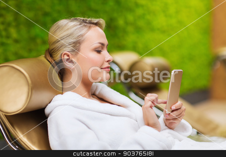 beautiful young woman with smartphone at spa stock photo, people, beauty, lifestyle, technology and relaxation concept - beautiful young woman in white bath robe with smartphone social networking at spa by Syda Productions