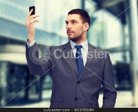 young businessman with smartphone stock photo, business, technology, internet and education concept - friendly young businessman with smartphone by Syda Productions