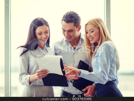 business team looking at clipboard stock photo, business and office concept - smiling business team looking at clipboard by Syda Productions