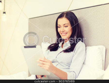 happy businesswoman with tablet pc in hotel room stock photo, business, technology, internet and hotel concept - happy businesswoman with tablet pc computer lying in hotel in bed by Syda Productions