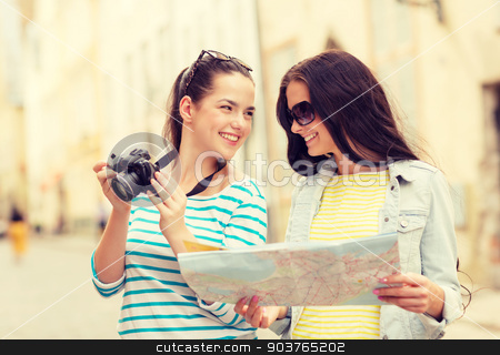 smiling teenage girls with map stock photo, tourism, travel, leisure, holidays and friendship concept - two smiling teenage girls with map and camera outdoors by Syda Productions