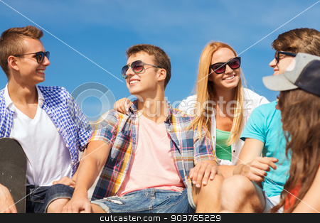 group of smiling friends sitting on city street stock photo, friendship, leisure, summer and people concept - group of smiling friends with skateboard sitting on city street by Syda Productions