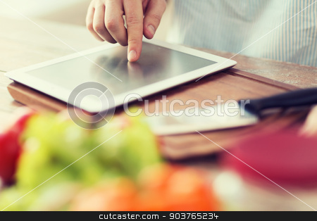 closeup of man pointing finger to tablet pc stock photo, cooking, technology and home concept - closeup of man pointing finger to tablet pc computer by Syda Productions