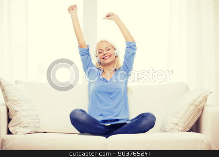 woman with tablet pc and headphones at home stock photo, home, music, technology and internet concept - smiling woman sitting on the couch with tablet pc computer and headphones at home by Syda Productions
