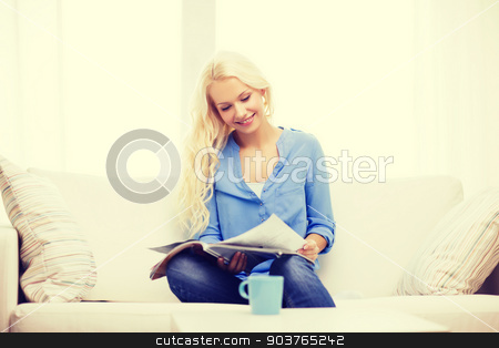 woman sitting on couch and reading magazine stock photo, home and leasure concept - smiling woman sitting on couch and reading magazine at home by Syda Productions