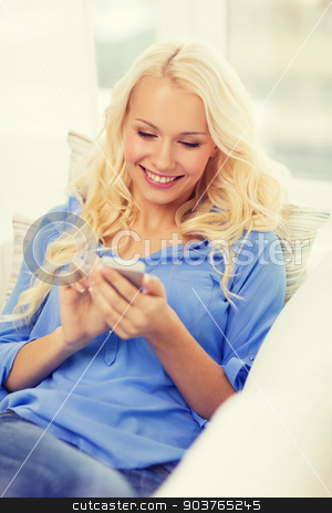 smiling woman with smartphone at home stock photo, home, technology and internet concept - smiling woman with smartphone lying on couch at home by Syda Productions