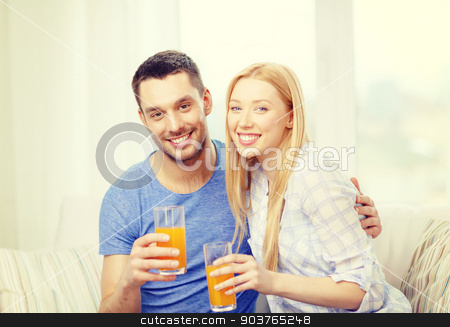 smiling happy couple at home drinking juice stock photo, love, family, healthy food and happiness concept - smiling happy couple drinking juice at home by Syda Productions