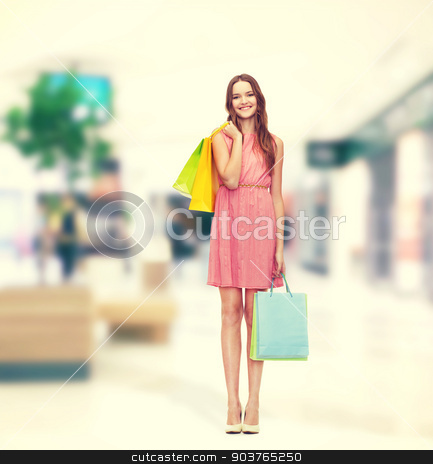 smiling woman in dress with many shopping bags stock photo, retail and sale concept - smiling woman in dress and high heels with many shopping bags by Syda Productions