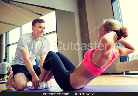 woman with personal trainer doing sit ups in gym stock photo, fitness, sport, training, gym and lifestyle concept - woman with personal trainer doing sit ups in gym by Syda Productions