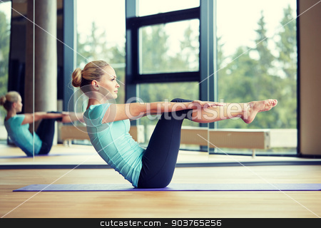 smiling woman doing exercises on mat in gym stock photo, fitness, sport, training and people concept - smiling woman doing abdominal exercises on mat in gym by Syda Productions