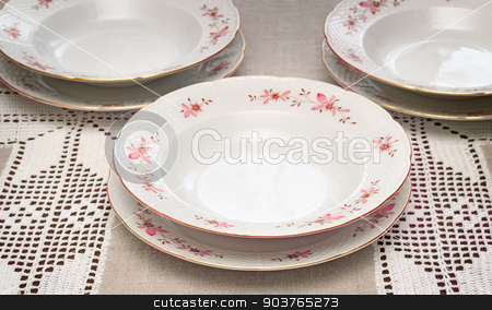 Tableware: a few white plates on the table. stock photo, On the table covered with a lace tablecloth, stand white plates , decorated with delicate ornaments. by Georgina198
