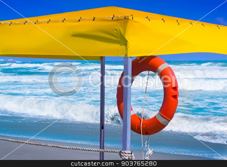 A lifeline to rescue drowning in the sea. stock photo, On the shore of a stormy sea under the awning hanging red lifeline to rescue the drowning. by Georgina198
