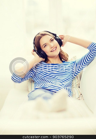 smiling young girl in headphones at home stock photo, technology, music and happiness concept - smiling young girl in headphones at home by Syda Productions
