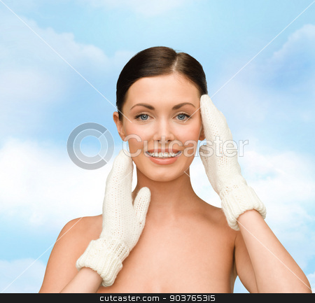 smiling young woman in white mittens stock photo, beauty, winter, people and health concept - smiling young woman in white mittens over blue sky background by Syda Productions