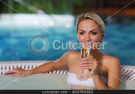 happy woman drinking champagne at swimming pool stock photo, people, beauty, spa, healthy lifestyle and relaxation concept - beautiful young woman wearing bikini swimsuit sitting with glass of champagne in jacuzzi at poolside by Syda Productions