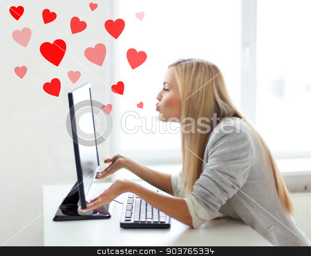 woman sending kisses with computer monitor stock photo, virtual relationships, online dating and social networking concept - woman sending kisses with computer monitor by Syda Productions