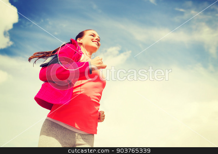 smiling young woman running outdoors stock photo, fitness, sport and lifestyle concept - smiling young woman with earphones running outdoors by Syda Productions