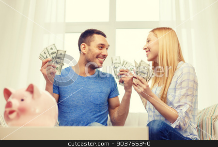 couple with money and piggybank ot table at home stock photo, love, family, finance, money and happiness concpet - smiling couple with money and piggybank ot table at home by Syda Productions