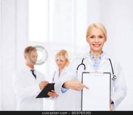 smiling female doctor with clipboard stock photo, healthcare and medicine concept - smiling female doctor with stethoscope pointing finger to clipboard and blank page by Syda Productions