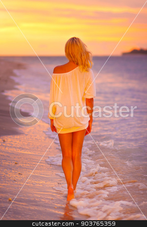 Lady on sandy tropical beach at sunset. stock photo, Beautiful blonde lady relaxing and enjoying vacations on the sandy beach at sunset. Romantic tropical holidays. by kasto