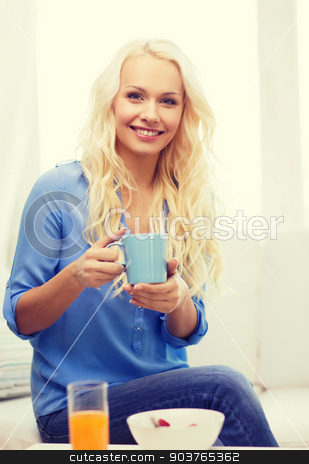 smiling woman with cup of tea having breakfast stock photo, healthcare, food, home and happiness concept - smiling woman with cup of tea, glass of juice and bowl of muesli having breakfast by Syda Productions