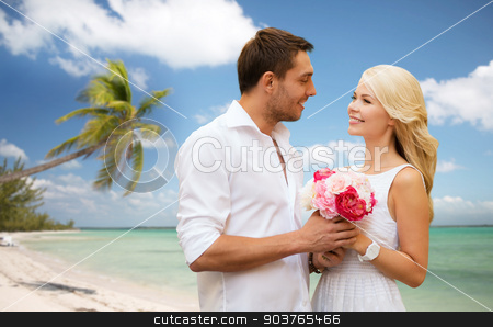 happy couple with flowers over beach background stock photo, holidays, travel, tourism, people and dating concept - happy couple with bunch of flowers over tropical beach background by Syda Productions