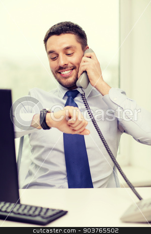 smiling businessman making call stock photo, business, office and technology concept - smiling businessman making call and looking at wristwatch at office by Syda Productions