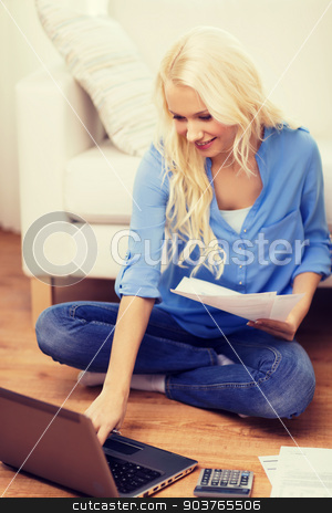 smiling woman with papers, laptop and calculator stock photo, tax, finances, technology, home and happiness concept - smiling young woman with papers, laptop computer and calculator at home by Syda Productions