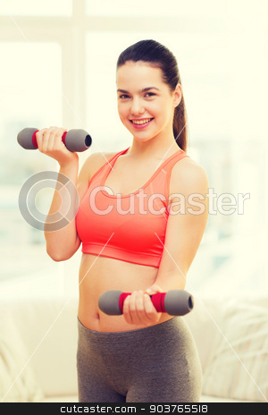 smiling teenage girl exercising with dumbbells stock photo, fitness, home and diet concept - smiling redhead girl exercising with heavy dumbbells at home by Syda Productions