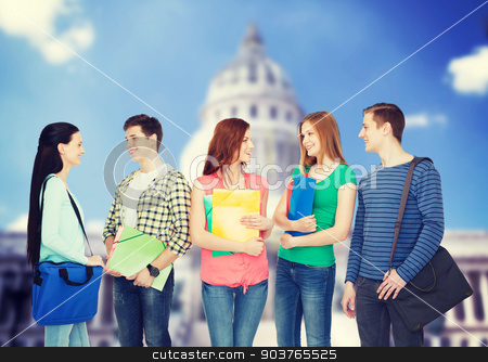 group of smiling students standing stock photo, education and people concept - group of smiling students with bags and folders having discussion by Syda Productions